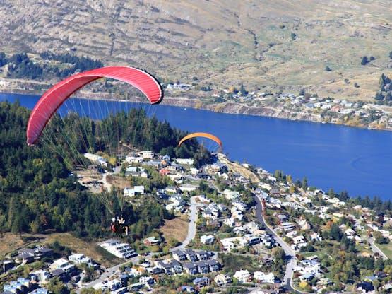 Paraglider sobrevoando a cidade de Queenstown, Nova Zelândia